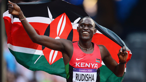 David Lekuta Rudisha, captain of Kenya's London 2012 Olympic Games team, celebrates with the Kenyan flag after winning gold and setting a new world record of 1.40.91 in the Men's 800m Final - photo by Mike Hewitt/Getty Images